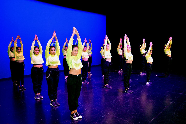 todas las chicas del grupo 2 vestidas con el uniforme para el baile en el escenario con fondo azul
