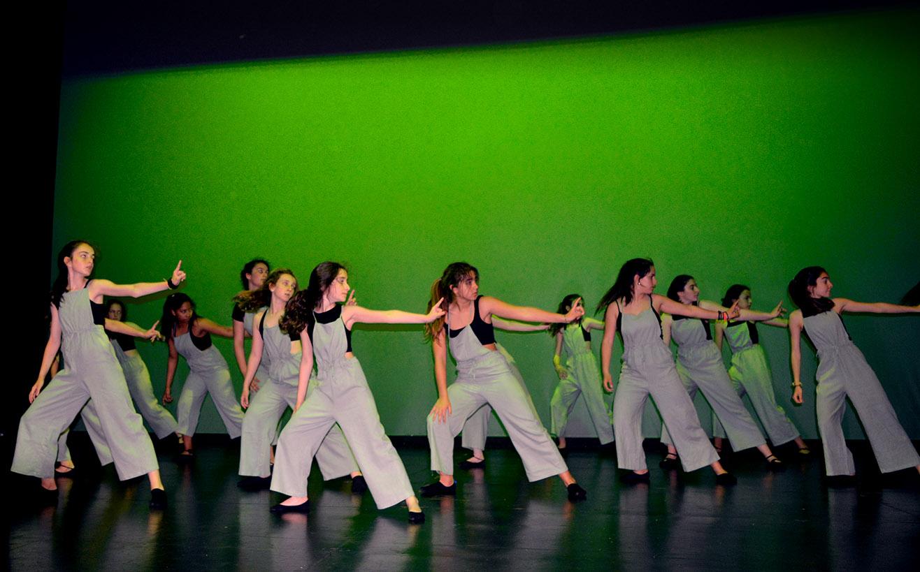 chicas del grupo 3baile con el fondo verde y peto gris con el brazo extendido