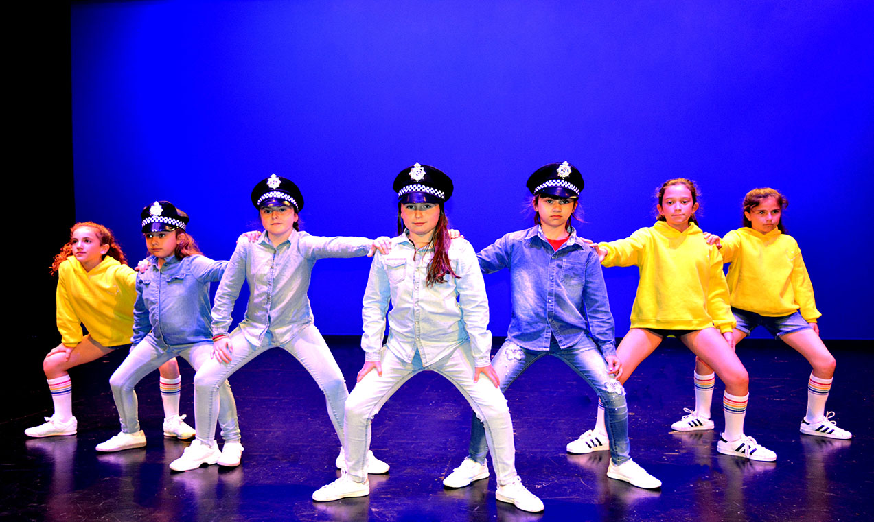 chicos de hip hop vestidos de policias con el fondo azul posando con chicas de amarillo