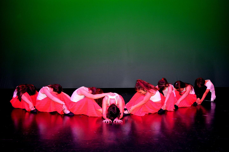 niños del grupo 2 figura en el suelo vestidos de rosa y fondo verda