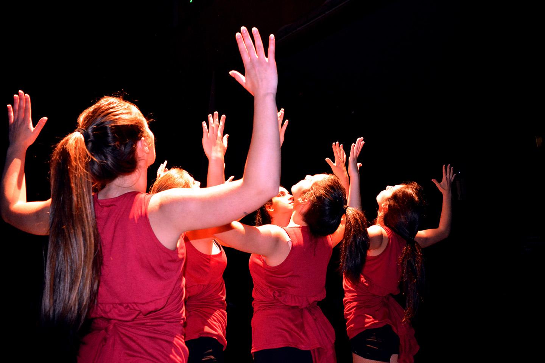 Baile con las manos en alto y foco de luz directo sin difusor