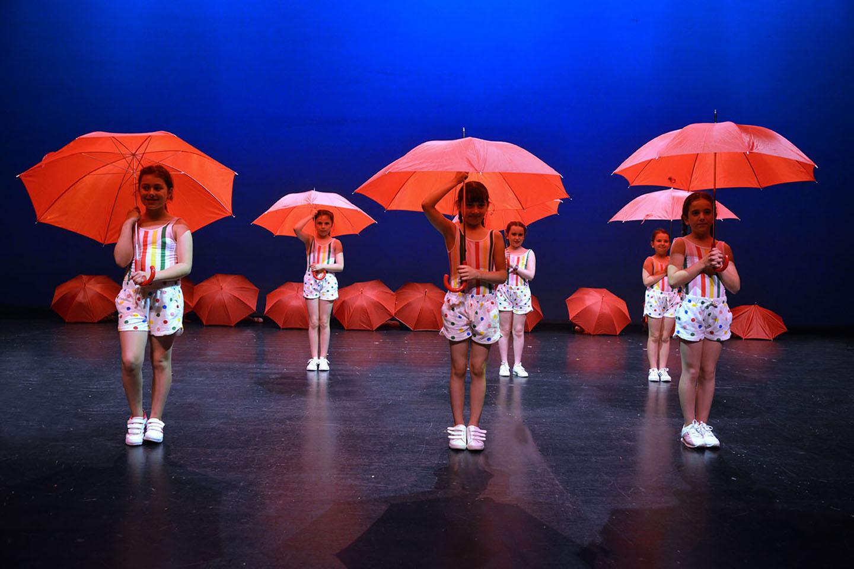 Baile de los paraguas rojos con niñas vestidas de llunares de colores
