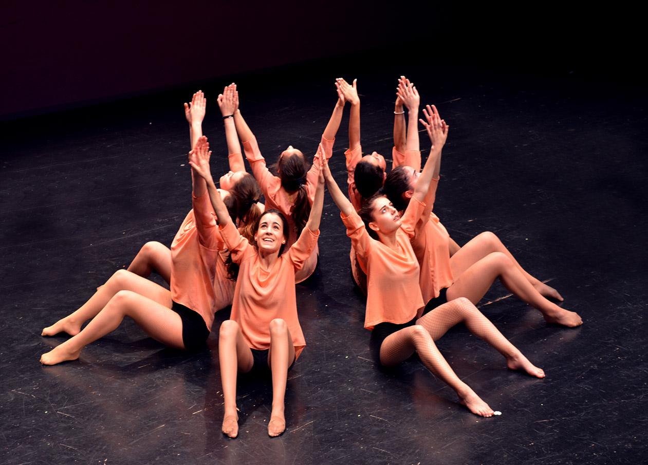 GRupo Santander Contemporaneo sentadas en el suelo en circulo con los brazos hacia arriba