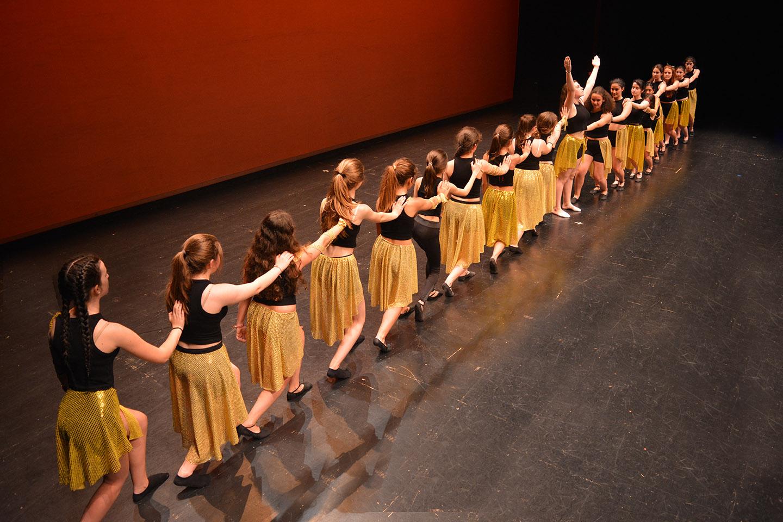 bailarinas traje negro y dorado fila india